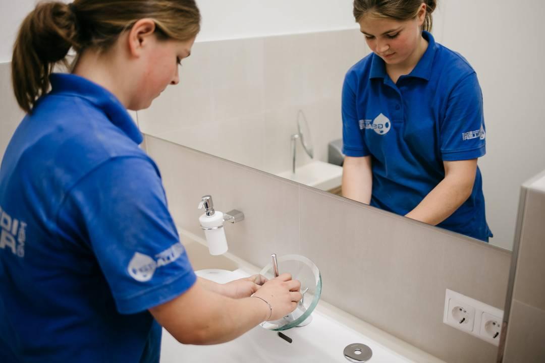 Mitarbeiterin arbeitet an Waschbeckenarmatur